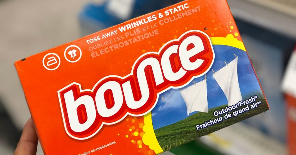 person holding up an orange box of outdoor fresh scented bounce dryer sheets