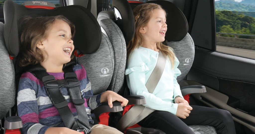 2 children sitting in grey and black car seats inside a car looking out the window