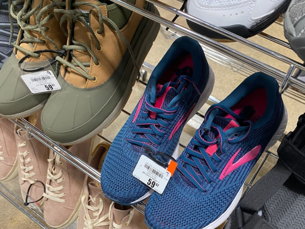 women's green and tan duck boots and women's blue and pink sneakers on shoe rack display in store