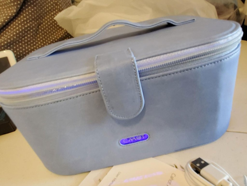 blue UV sanitizer cosmetics bag with zipper and magnetic closure and handle on top