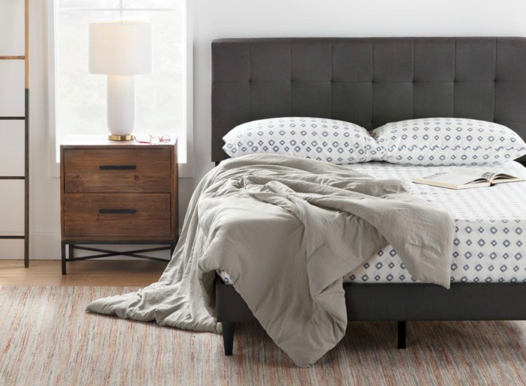 unmade bed with dark tufted headboard