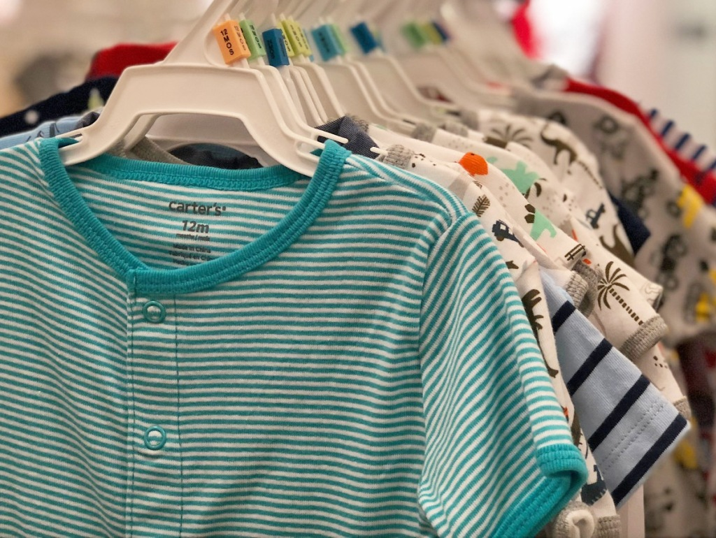 multiple Cater's baby rompers on hangers on store display rack