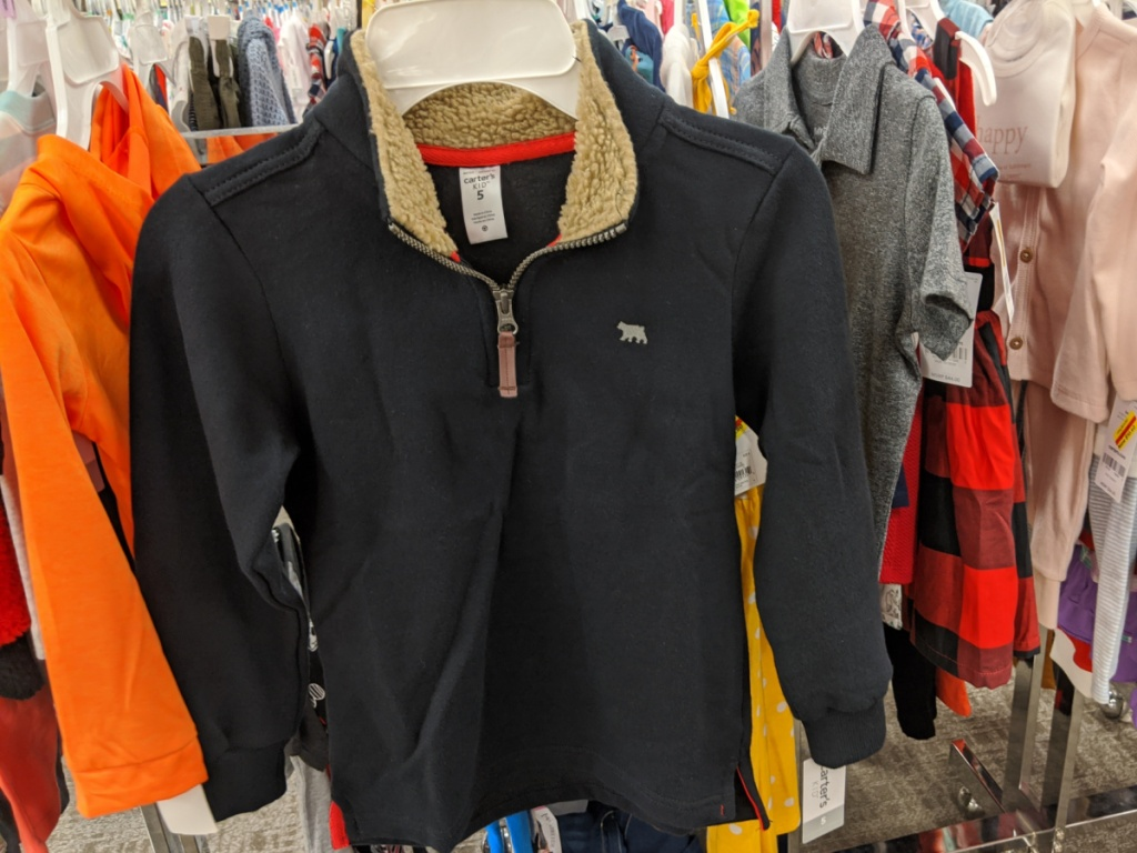 boys black pullover sweater hanging in store