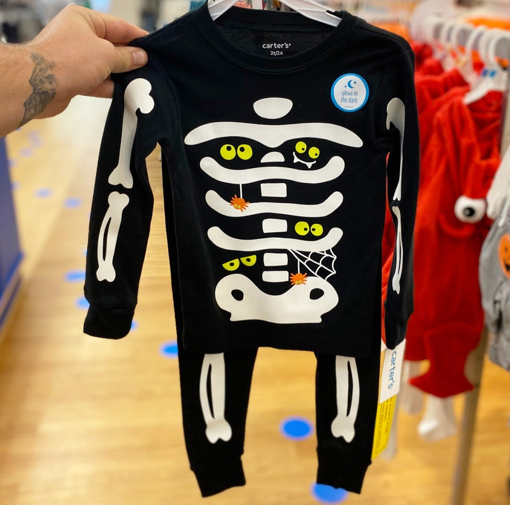 person holding up a pair of skeleton printed pajamas on a hanger