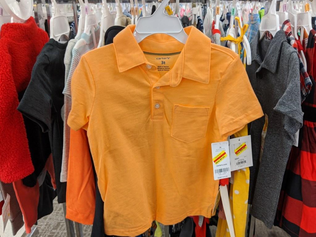 toddler boys orange polo shirt hanging in store
