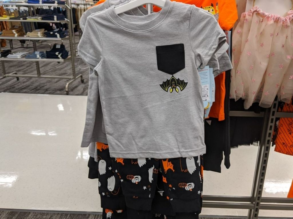 kids short sleeved shirt and pants set on hanger at store featuring Halloween bat graphics