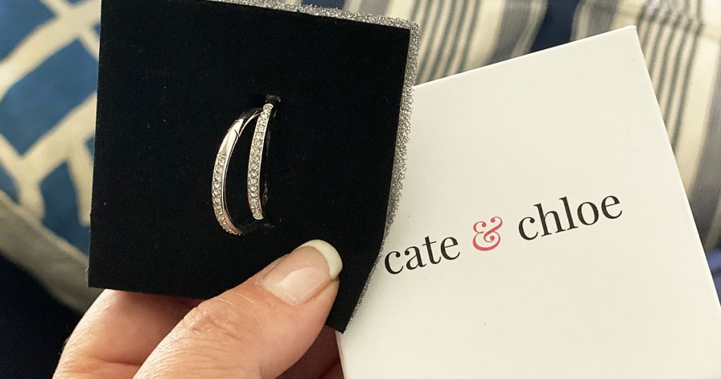 woman holding a pair of white gold sparkly hoop earrings with the cate & chloe jewelry box they're packaged in