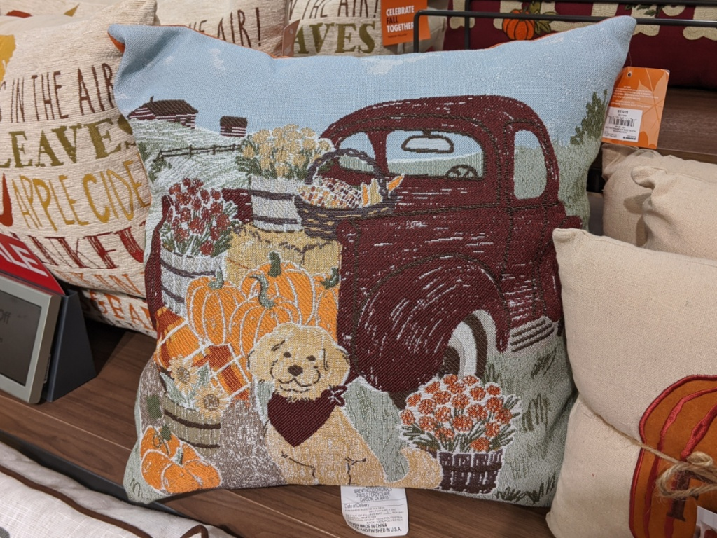 Fall themed dog and truck throw pillow on table in store