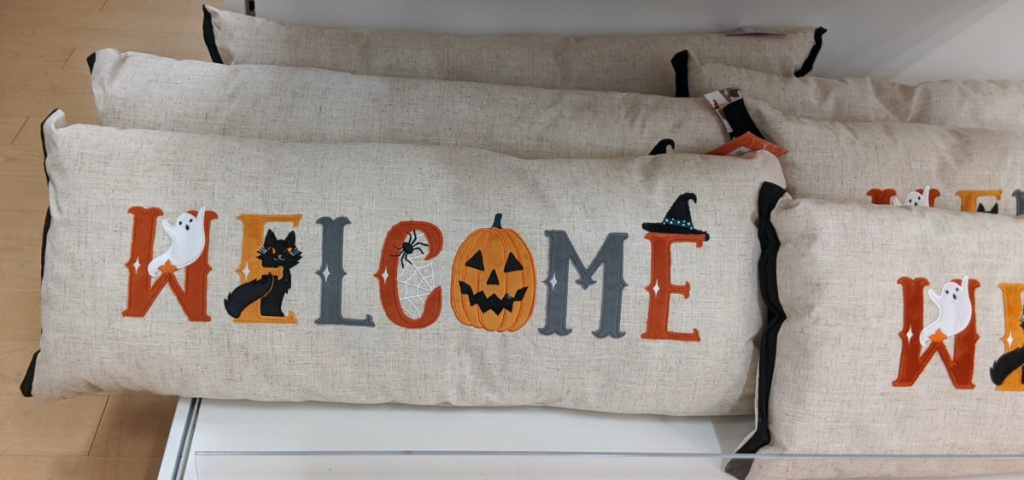 Welcome Halloween-themed throw pillows on store shelf