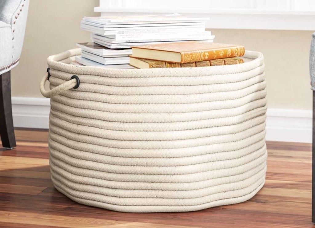 white woven fabric basket on hardwood floor with books inside