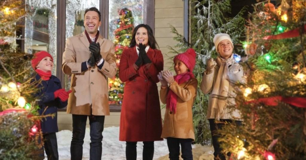 family standing outside among Christmas trees