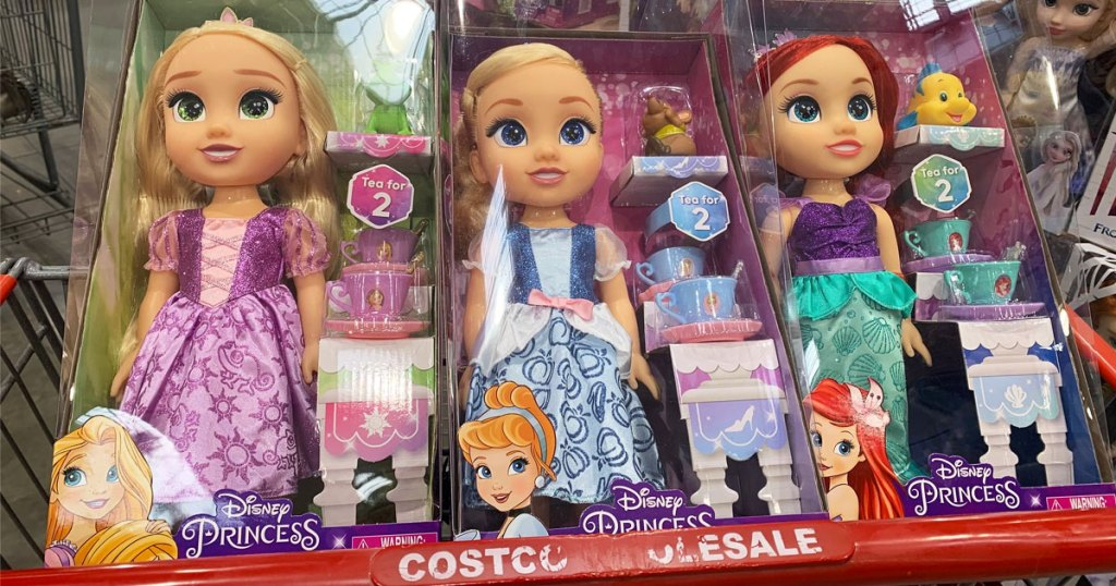 three Disney princess dolls in child seat area of Costco shopping cart