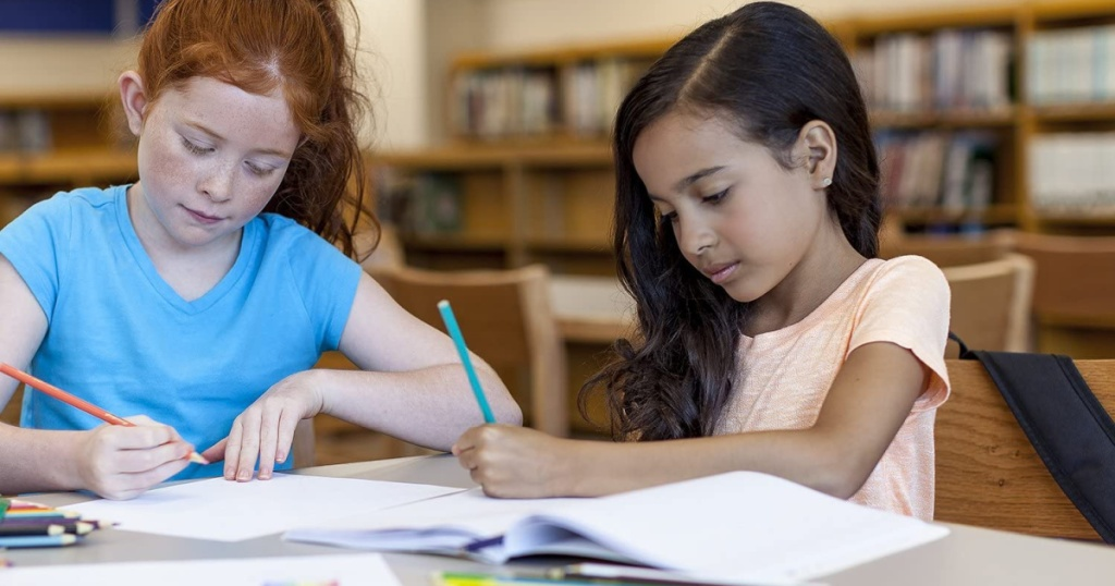 girls using colored pencils in library