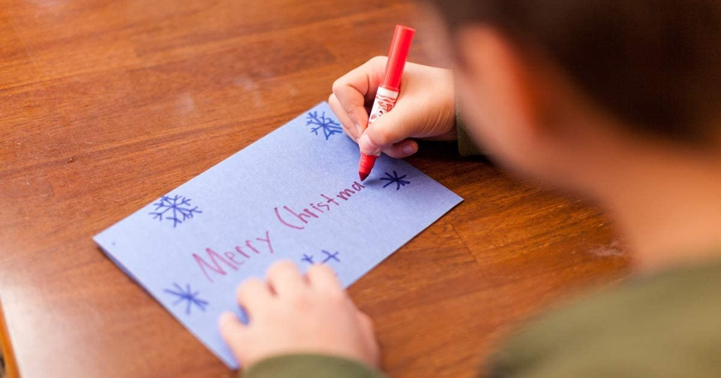 boy writing Merry Christmas on construction card with orange marker
