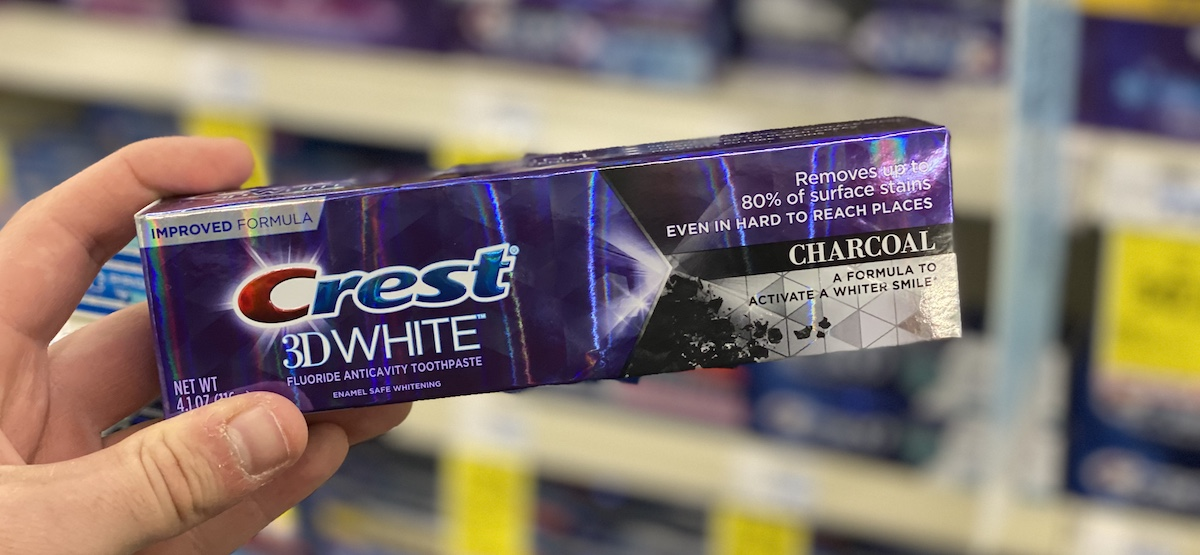 hand holding box of Crest 3D White Charcoal toothpaste