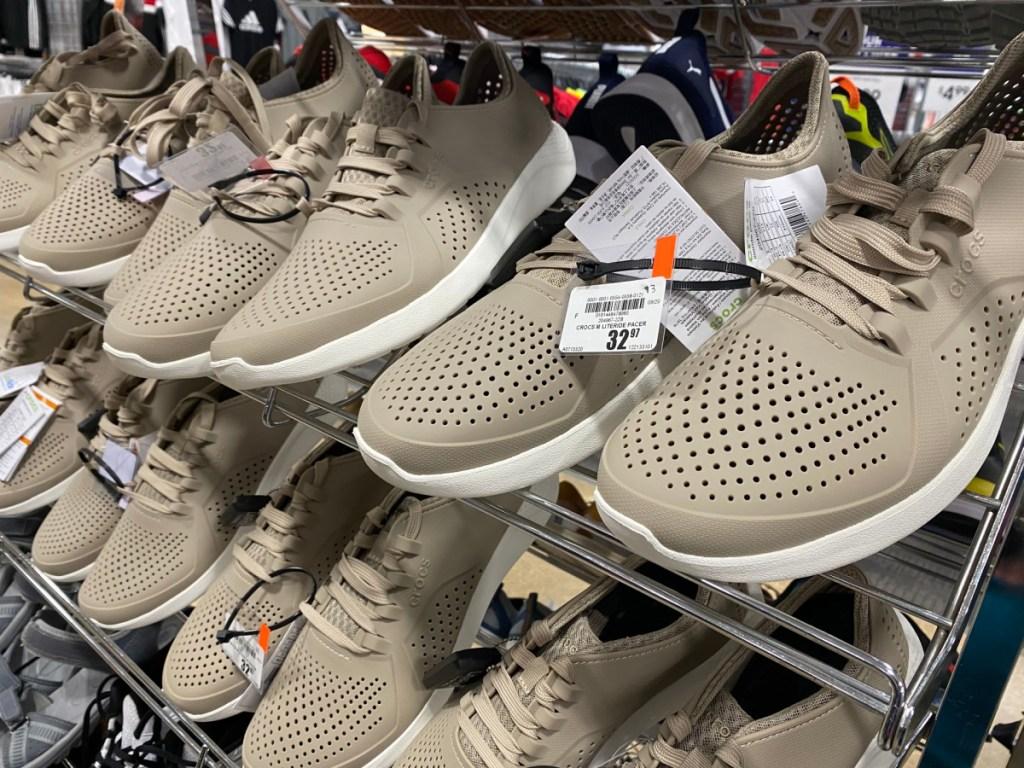 men's tan sneakers on shoe rack display in store
