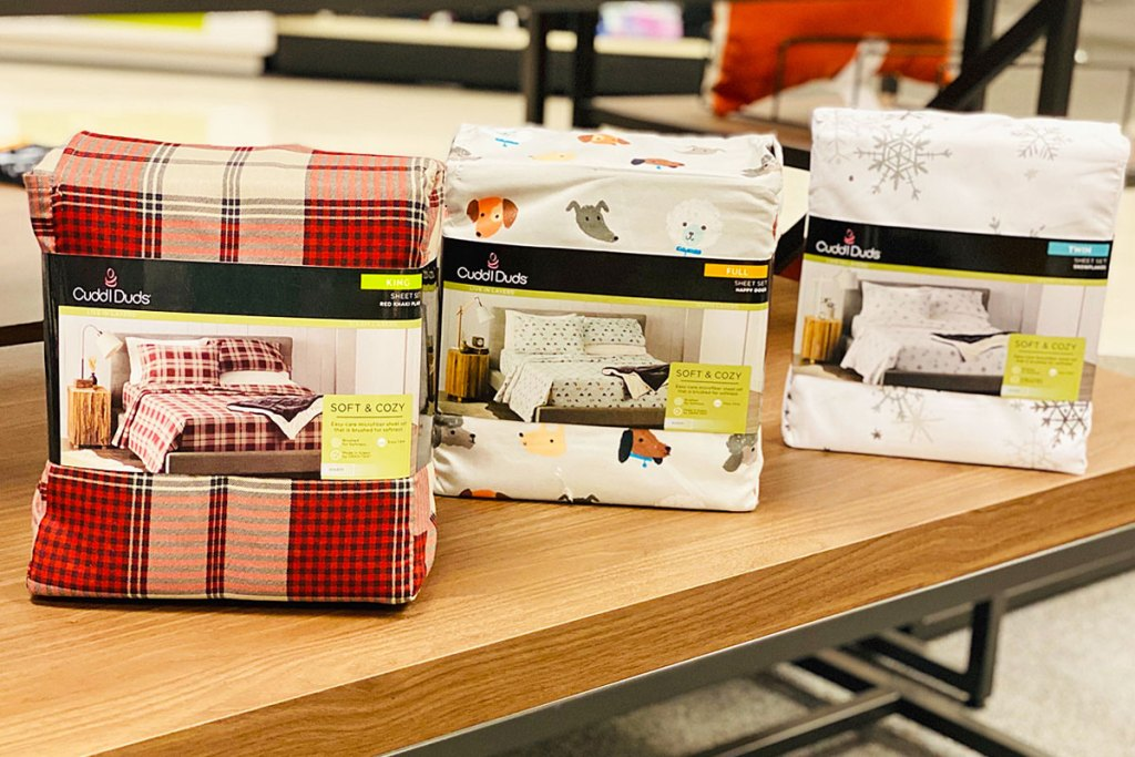 three sets of printed flannel sheet sets on a Kohl's display table