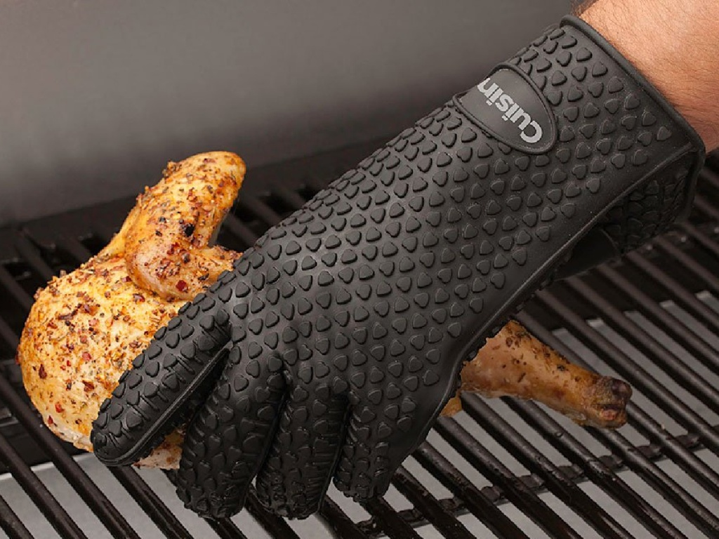hand in black silicone glove picking up cooked chicken on grill