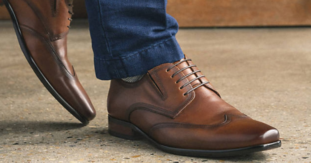 man wearing jeans and a pair of brown leather wingtip oxford shoes