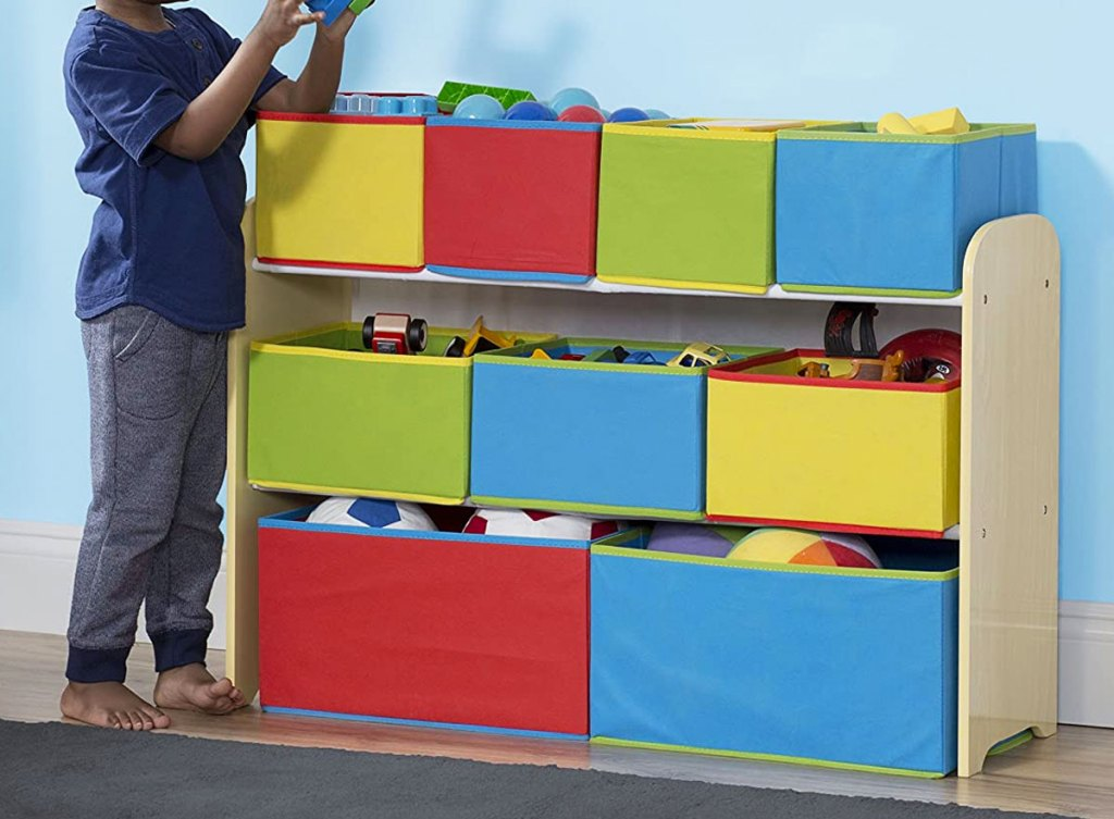boy standing next toy organizer with nine colorful fabric bins