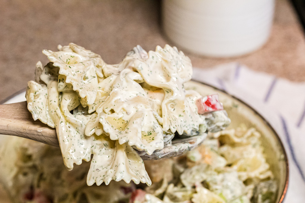 dill pickle pasta salad on wooden spoon