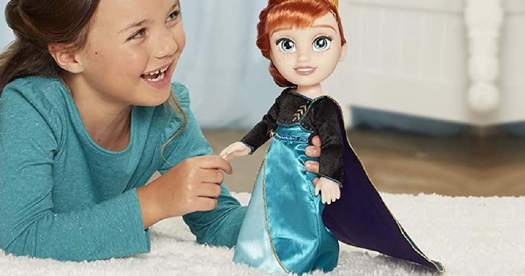 girl playing with Disney princess doll on carpet