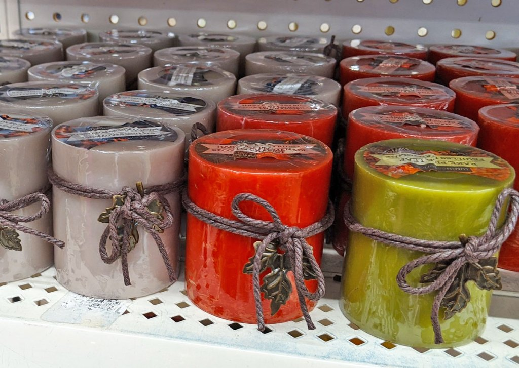 silver, red, and green pillar candles with rope bows and metallic leaves on each one