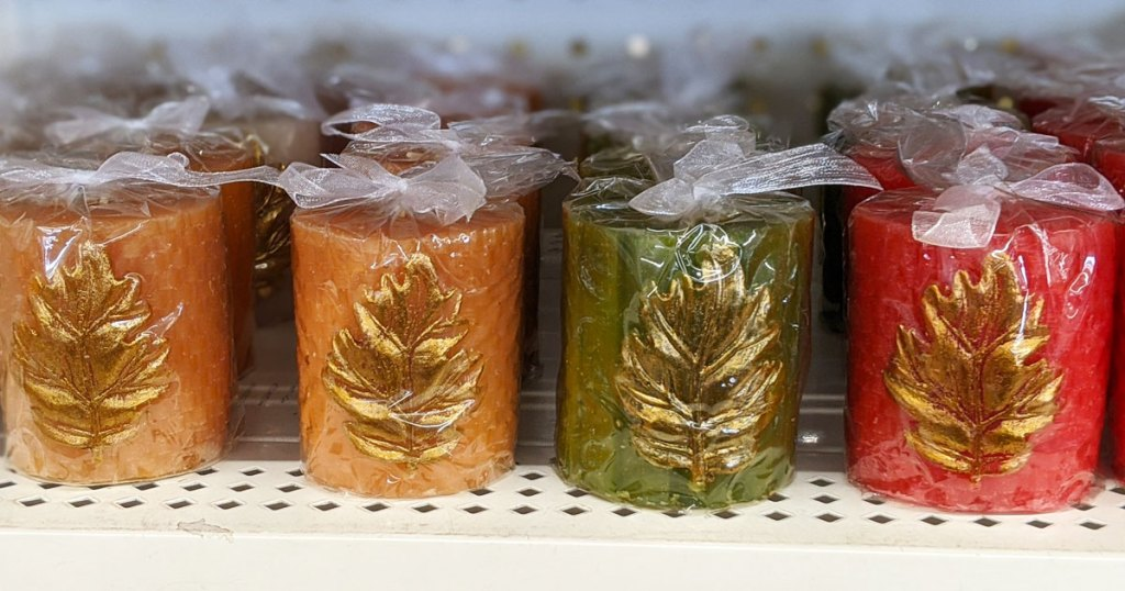 red, green, and yellow votive candles with gold leaves on them