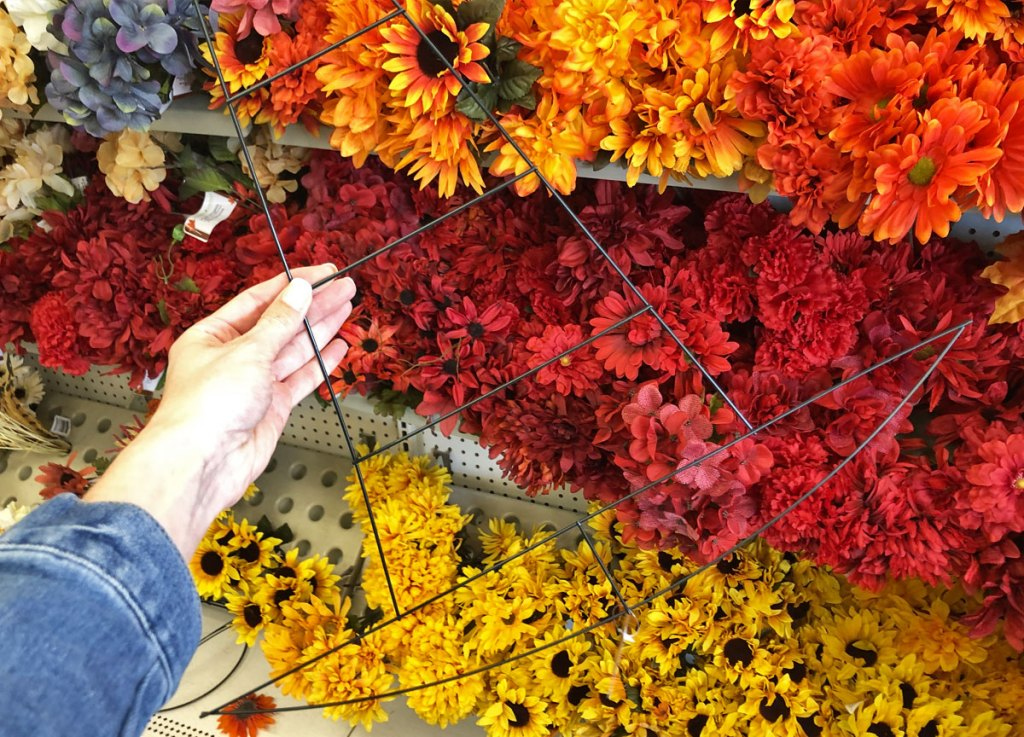 person holding up halloween witch's hat shaped wire wreath form in front of silk flowers