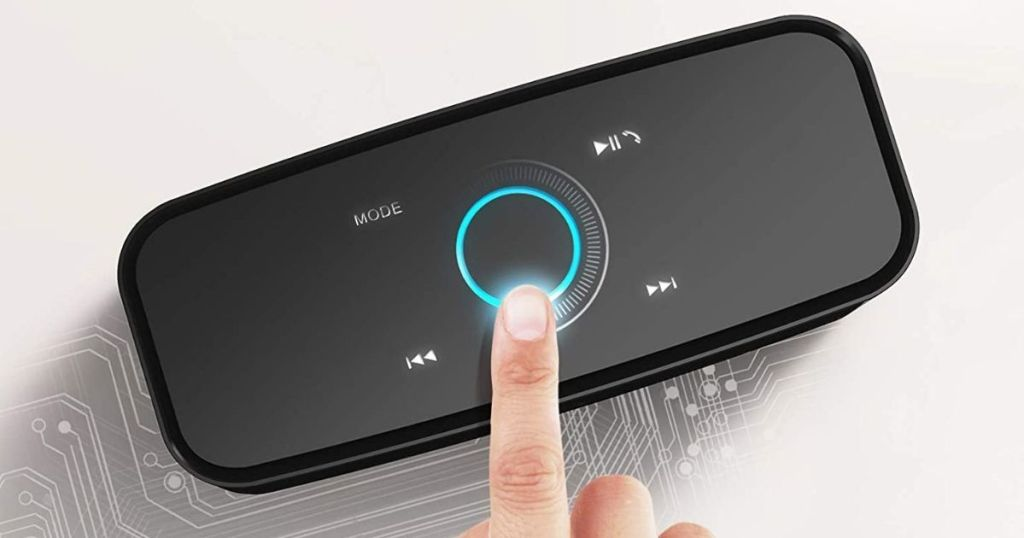 finger touching the top of a speaker