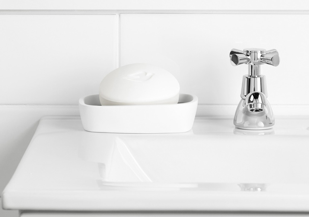 white bathroom sink with bar of dove soap in soap dish