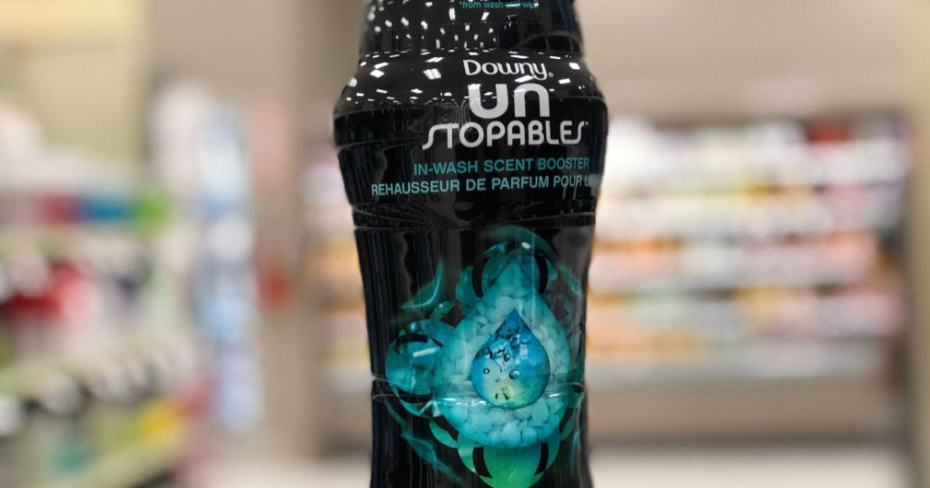 person holding up black and blue bottle of downy unstoppables laundry scent booster beads