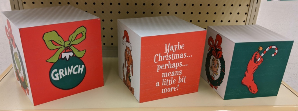 three Grinch Christmas boxes on store shelf