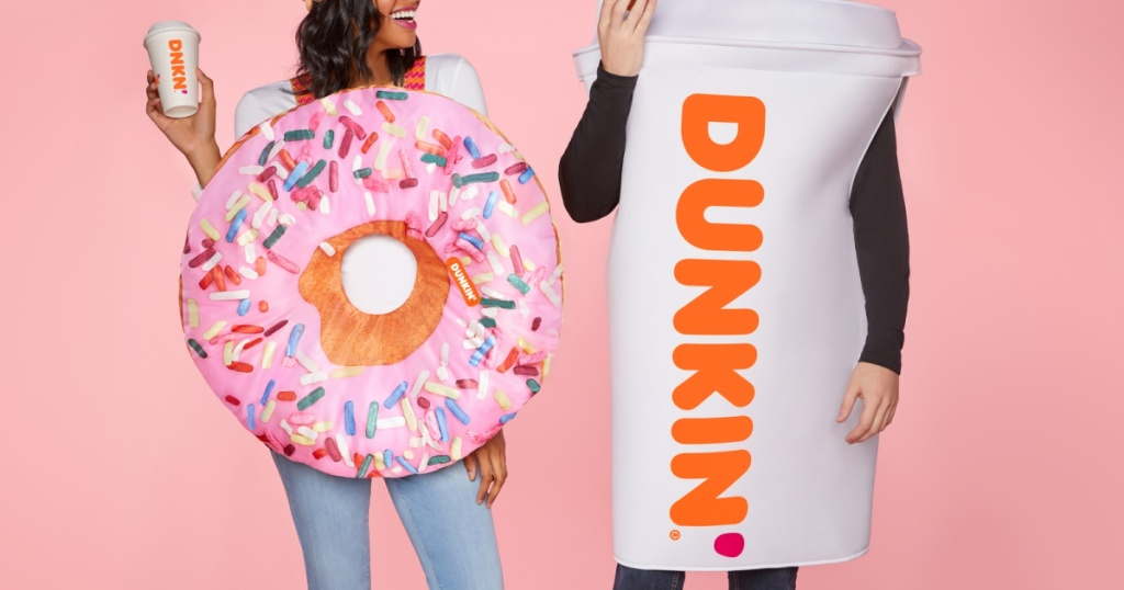 woman in pink sprinkle donut costume holding coffee and man in Dunkin' coffee cup costume and light pink background