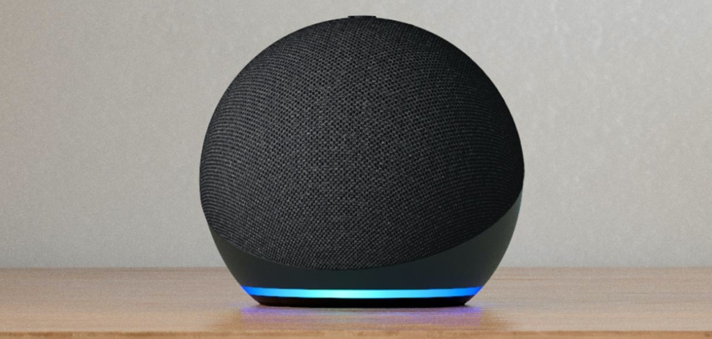 black smart speaker with blue light on wood table