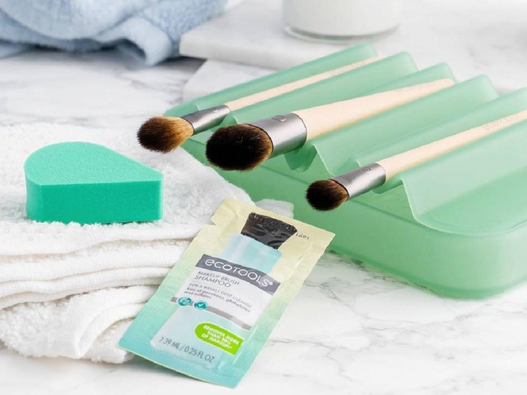 makeup brushes sitting on green drying rack, green sponge, and brush shampoo