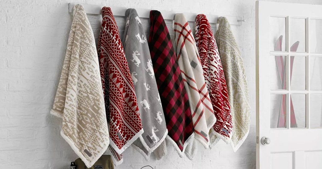 various printed sherpa throw blankets hanging on hooks by front door