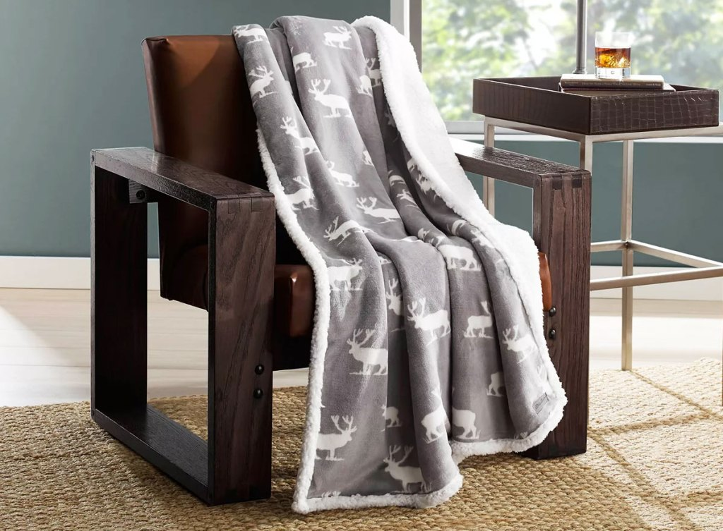 grey sherpa throw blanket with moose print draped on leather chair