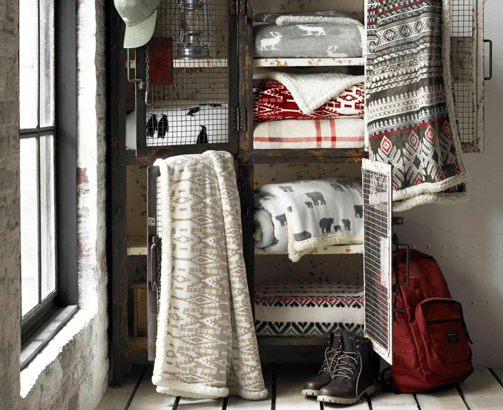 sherpa throw blankets folded and hanging on sides of storage locker with winter gear