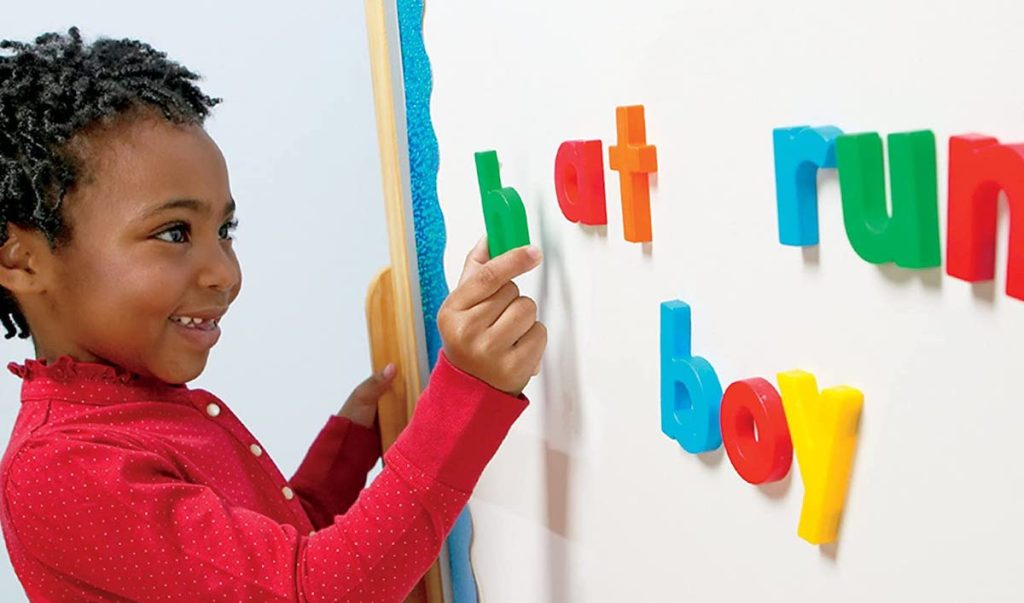 kid spelling words with alpha magnets