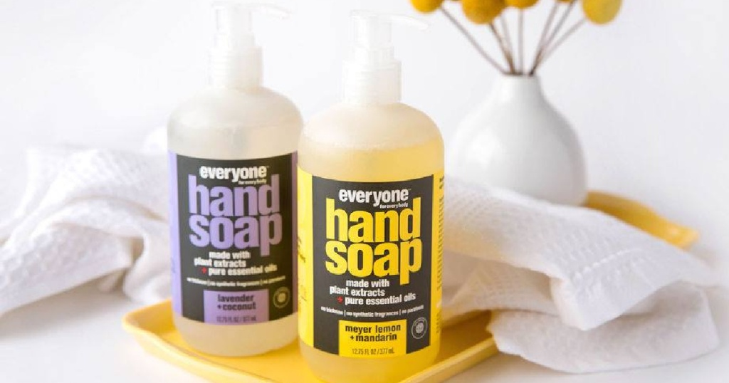 2 botol Sabun Tangan Semua Orang yang diletakkan di kamar mandi di samping handuk dan vas dengan bunga
