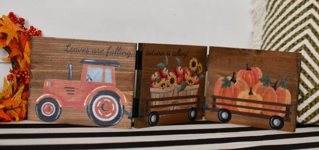 hinged sign with tractor pulling wagons of apples and pumpkins
