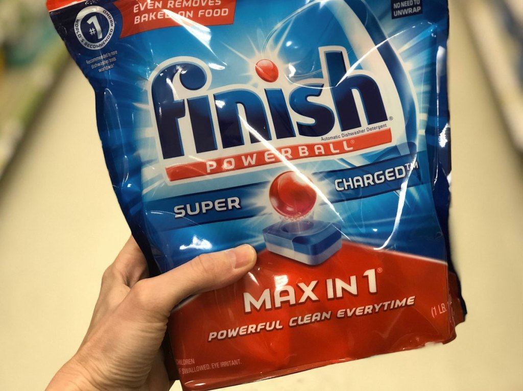 person holding up a blue and red bag of finish dishwasher detergent tablets