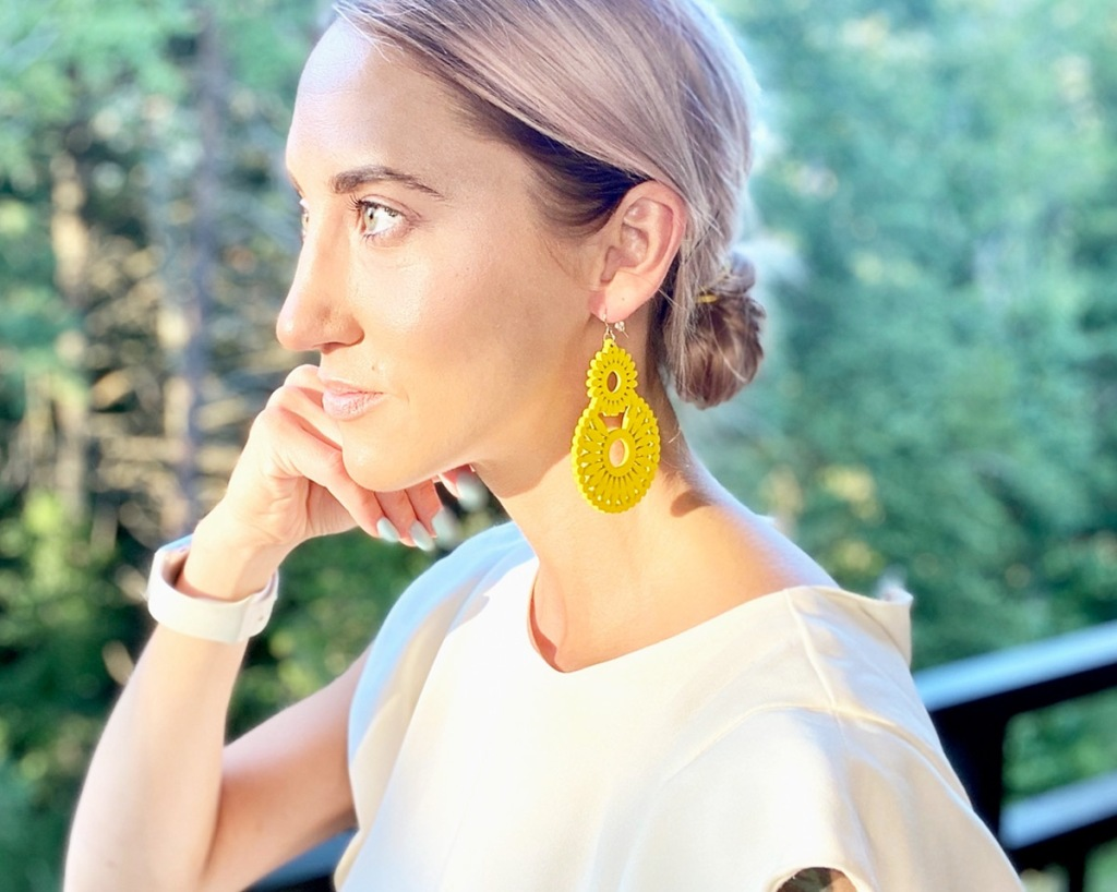 woman with blonde hair wearing white shirt and pair of yellow wood earrings