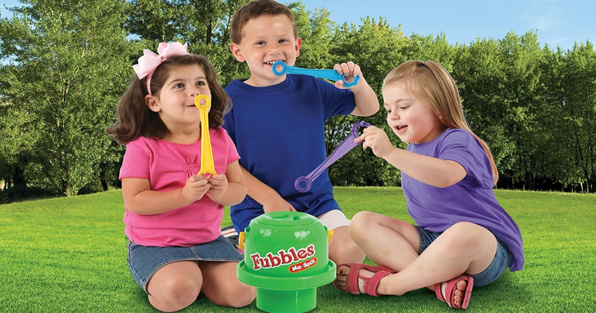 Fubbles no spill bubble bucket with 3 wands. three kids sitting on the grass blowing bubbles outside