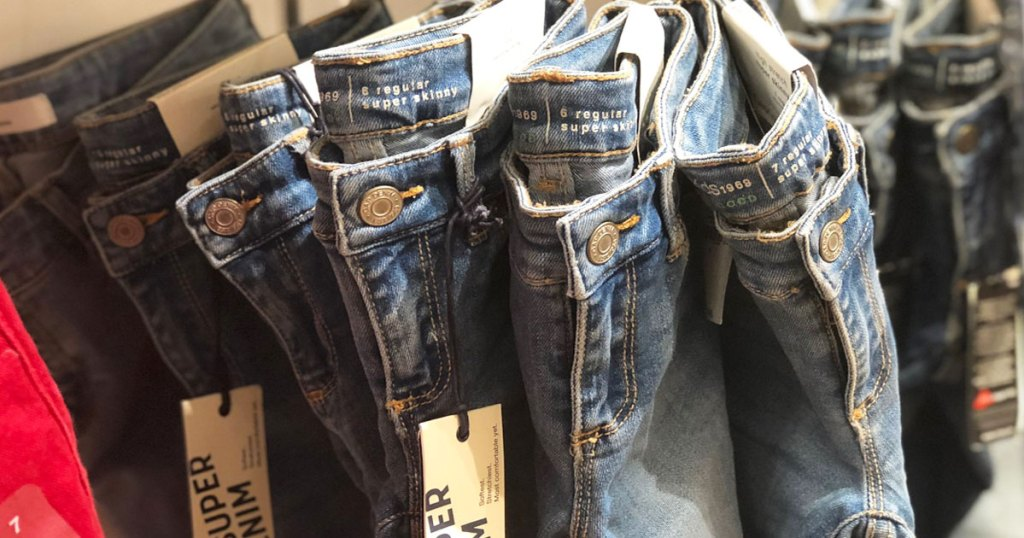 pairs of gap kids jeans hanging from hooks on store display