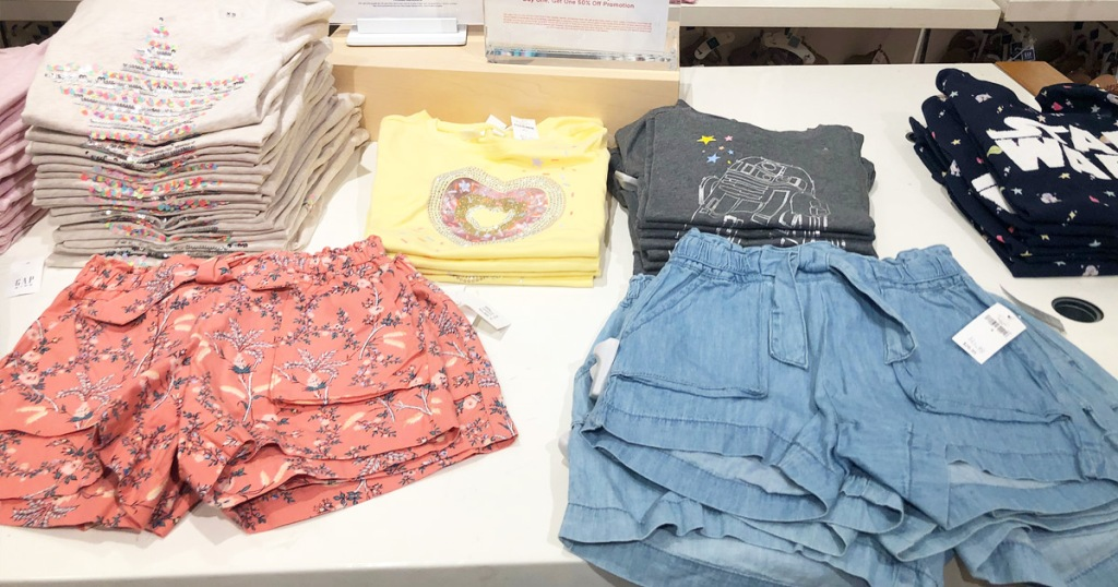 white display table with folded girls shirts and shorts