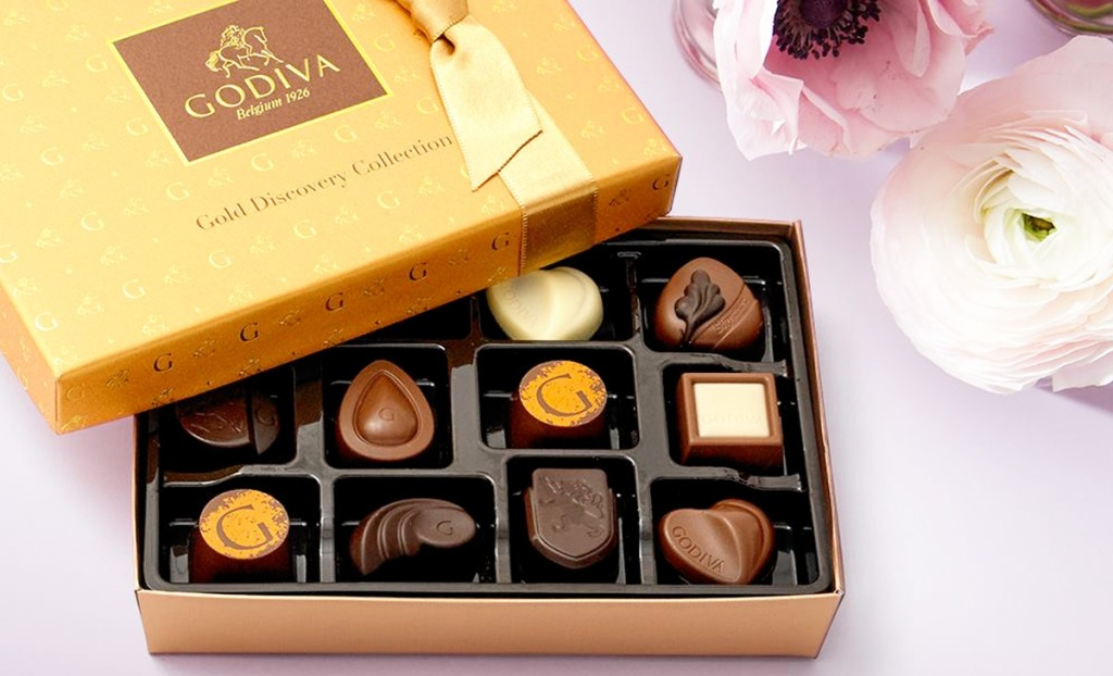 gold box of assorted godiva chocolates with pink flowers next to it
