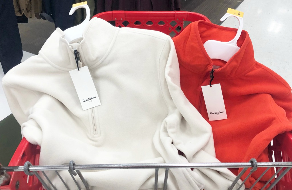 red and white colored men's fleece quarter-zip jackets in a red target shopping cart