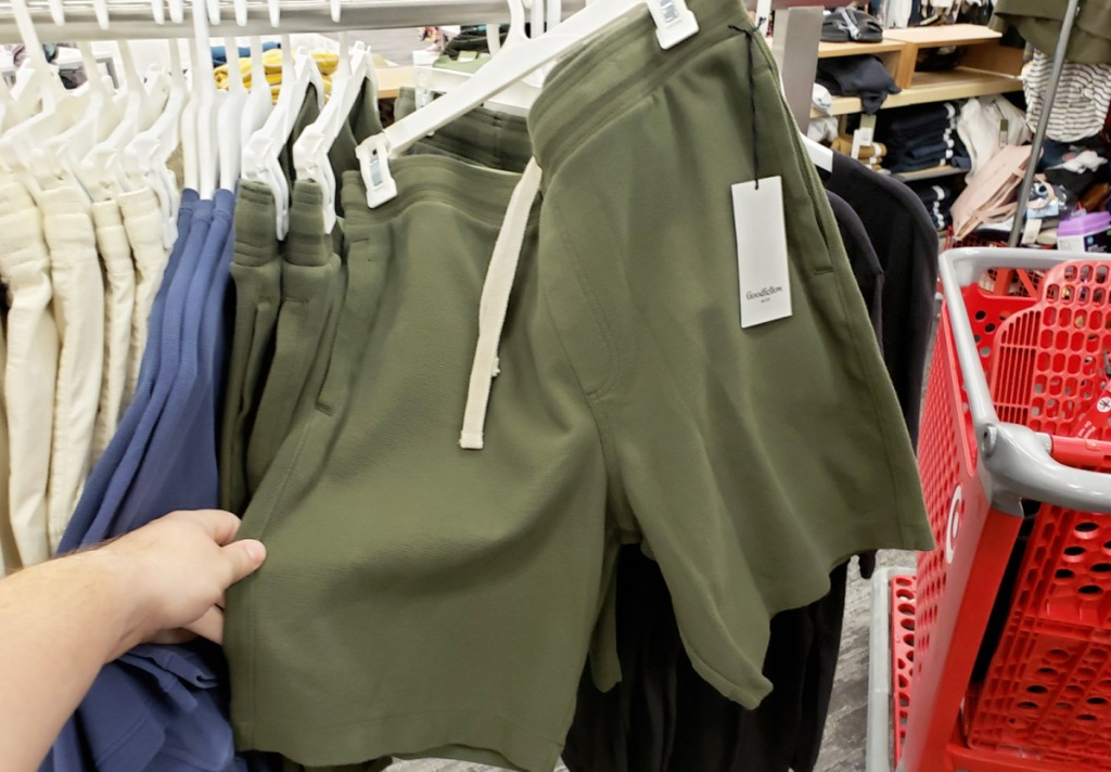 person holding a pair of olive green men's lounge shorts on store display